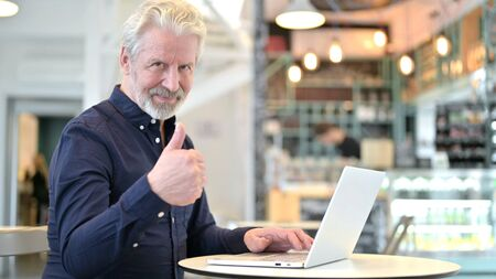 Thumbs up by Old Man with Laptop in Cafe