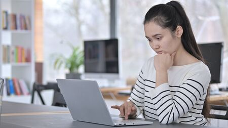 Pensive Young Asian Woman using Laptop in Office