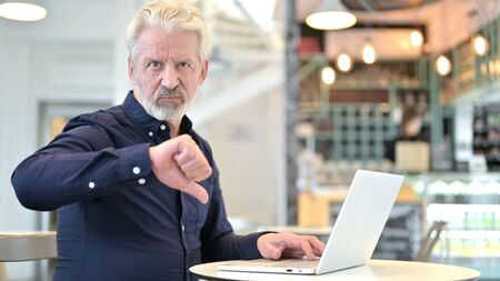 Thumbs Down by Old Man using Laptop in Cafe
