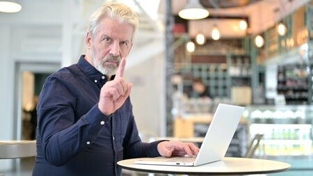 No, Finger Gesture by Old Man with Laptop in Cafe