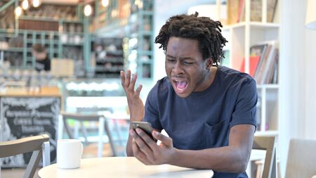 Screaming African Man Upset by Failure on Smartphone in Cafe