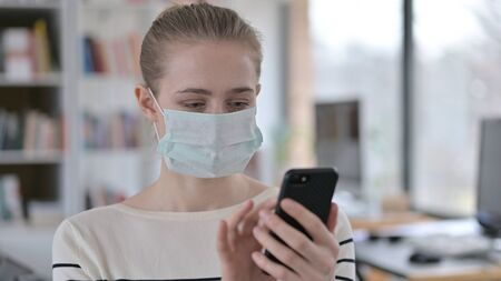 Portrait of Young Woman with Face Mask using Smartphone