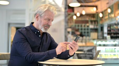 Focused Old Man Using Smartphone in Cafe