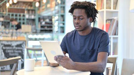 African Man using Digital Tablet in Cafe