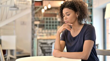 Pensive Young African Woman Thinking in Cafe Archivio Fotografico - 150120529