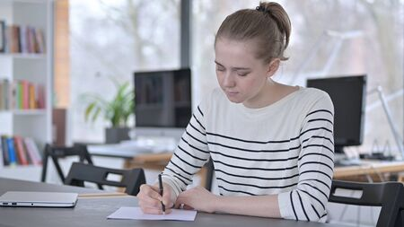 Thoughtful Young Woman doing Paperwork in Library