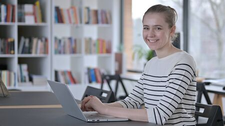 Young Woman Smiling at Camera in Library Zdjęcie Seryjne