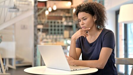 Pensive Young African Woman using Laptop in Cafe Archivio Fotografico