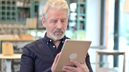 Portrait of Professional Old Man using Digital Tablet