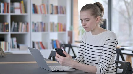 Smartphone use by Young Woman with Laptop in Library Zdjęcie Seryjne