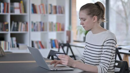 Online Shopping on Laptop by Young Woman, Library