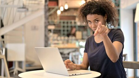 Young African Woman with Laptop Pointing with Finger
