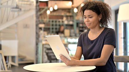Digital Tablet use by Beautiful Young African Woman in Cafe Archivio Fotografico