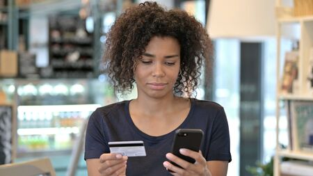 African Woman Shopping Online via Smartphone