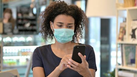 African Woman with Face Mask Using Smartphone