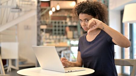 Young African Woman with Laptop showing Thumbs Down 스톡 콘텐츠