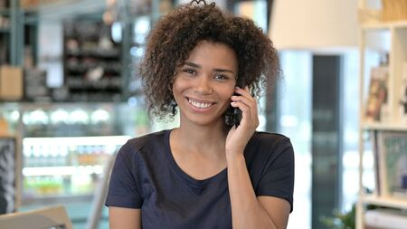 Young African Woman Talking on Smartphone