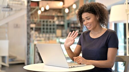 Video Chat on Laptop by Young African Woman in Cafe