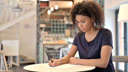 Thoughtful Young African Woman doing Paperwork in Cafe