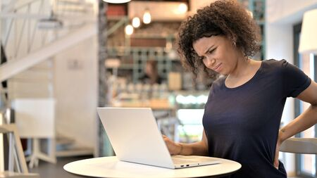 Young African Woman with Back Pain using Laptop in Cafe Archivio Fotografico