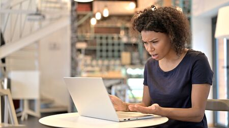 Young African Woman Reacting to Loss on Laptop in Cafe Archivio Fotografico