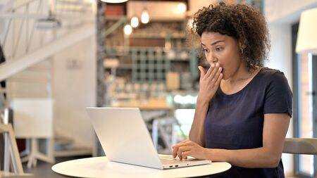 African Woman Feeling Shock on Laptop in Cafe