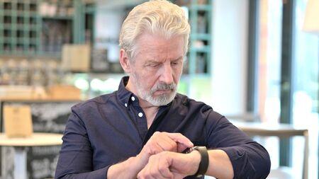 Portrait of Senior Old Man Using Smartwatch