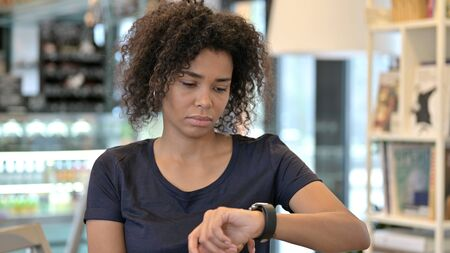 Serious Young African Girl using Smartwatch