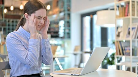 Young Woman with Headache using Laptop in Cafe