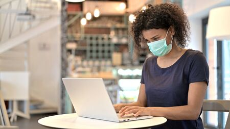 African Woman with Face Mask Working on Laptop in Cafe Standard-Bild