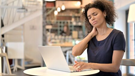 Young African Woman with Neck Pain using Laptop in Cafe