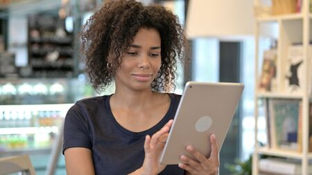 Beautiful Young African Woman using Digital Tablet Фото со стока