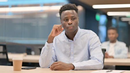 African Businessman Sitting in Office Thinking Foto de archivo