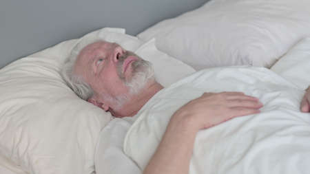 Pensive Senior Old Man Laying in Bed Thinking Imagens