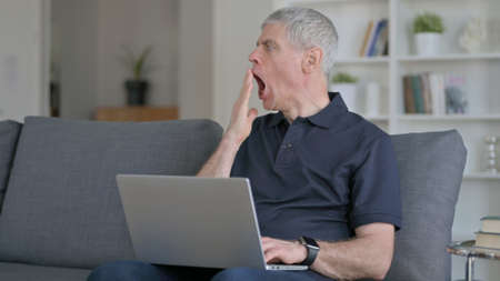 Tired Middle Aged Man with Laptop Yawning, Need Rest on Sofa