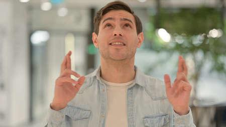 Portrait of Young Man Praying, Fingers Crossed Reklamní fotografie
