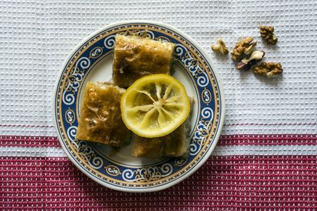 baklawa: Baklava dessert decorated with lemon slice and walnuts. Top view. Stock Photo