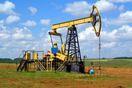 jack pump: Oilfield Pump Jack with a bright blue sky and clouds