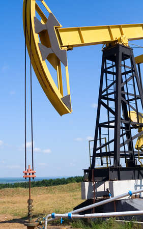 Oilfield Pump Jack with a bright blue sky and clouds  photo