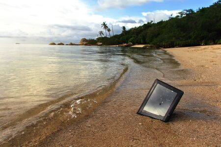 crashed: crashed tablet is washed by the waves on the beach