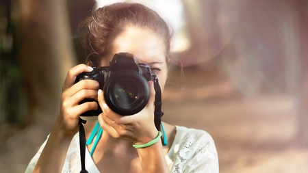 clinging: Happy young girl taking a photo looking in dslr camera Stock Photo