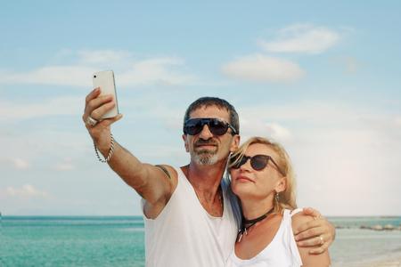 Senior couple doing a self-portrait at the beach Stock Photo