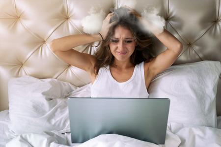 Giovane donna che osserva nello schermo del laptop e che la tiene testa cotta a vapore