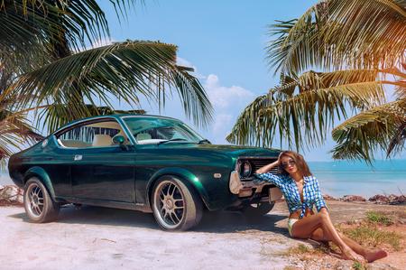 若い魅力的なモデルはレトロな車の近くに座っています。 写真素材