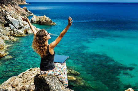 Happy lady freelancer sitting with laptop on a high and raising her arms up