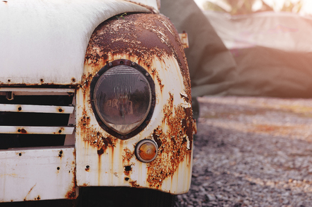 Detail of the front headlight of an rusty car outdoor