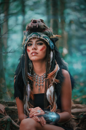 Futuristic indian woman portrait with wolf skull hat outdoors. Background blue wild forest Stock Photo