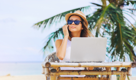 Young attractive woman in sunglasses and dress with hat working in laptop on the beach. Girl Freelancer working Imagens