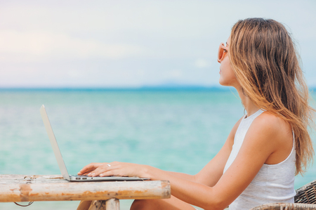 Young sexy woman freelancer in dress sitting at the table on ocean background, using laptop on the beach. Girl Freelancer working