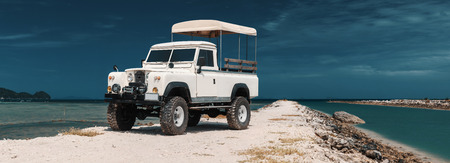 Panoramic photo of safari car on offroad , adventure trail. ocean, sky and clouds on background, With empty space for logo or text